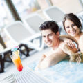 Couple drinking a cocktail by the swimming pool and relaxing