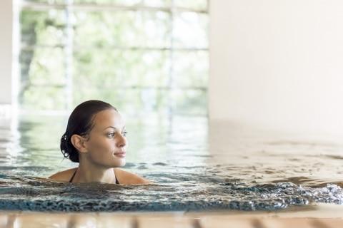 Im Schwimmbad eines Südtiroler Wellnesshotels seine Runden drehen und dabei das Bergpanorama genießen: das ist Entspannung pur.